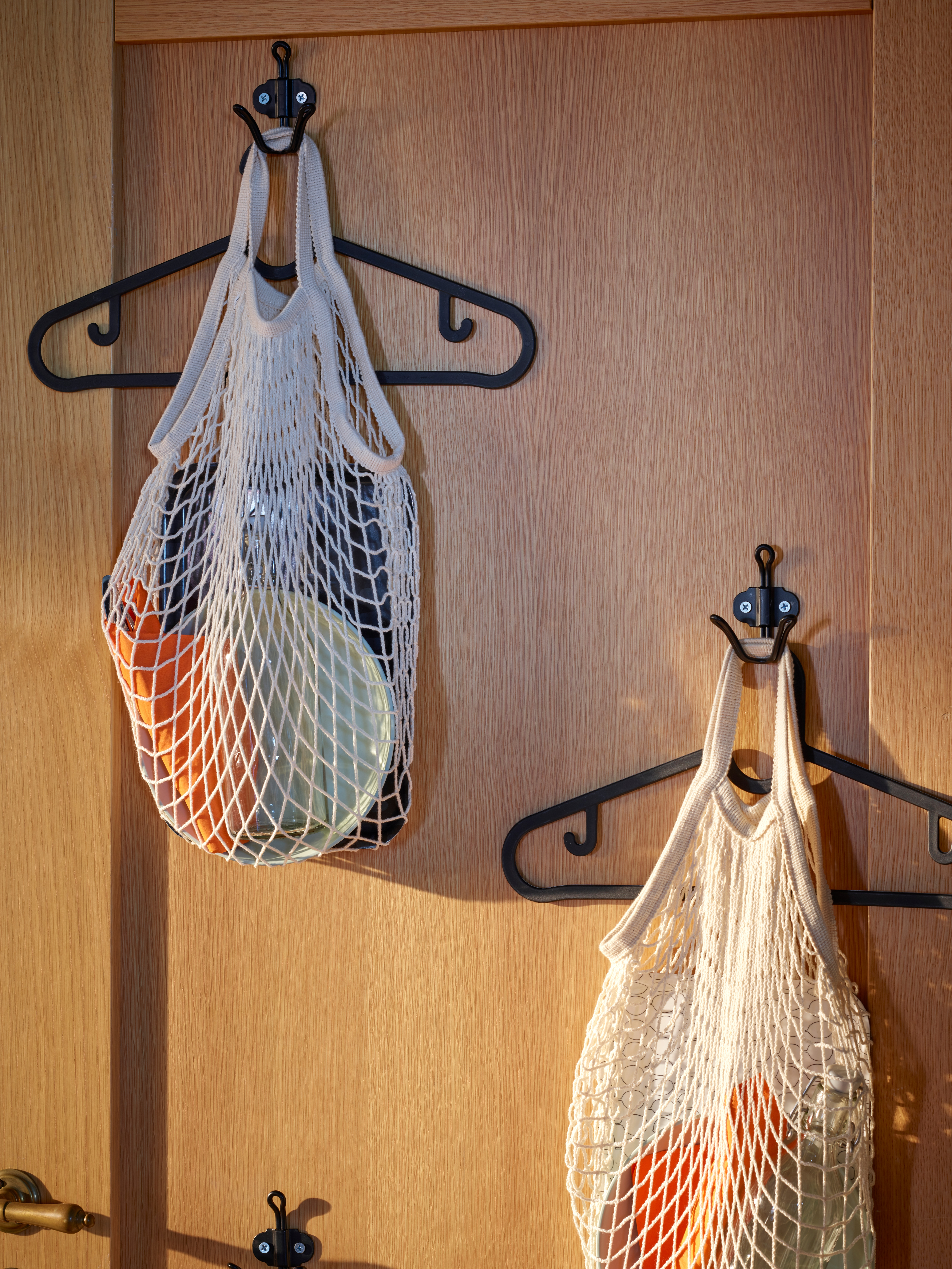 The inside of a wooden front door with two double scattered hooks, where each one has a hanger and a cotton KUNGFORS net bag.