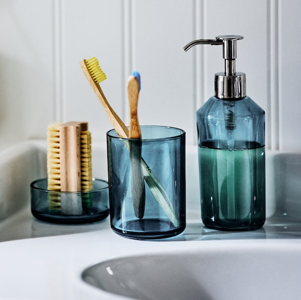 The SKISSEN  three-piece glass bathroom set on the side of a sink, holding a nail brush, toothbrushes and liquid soap.