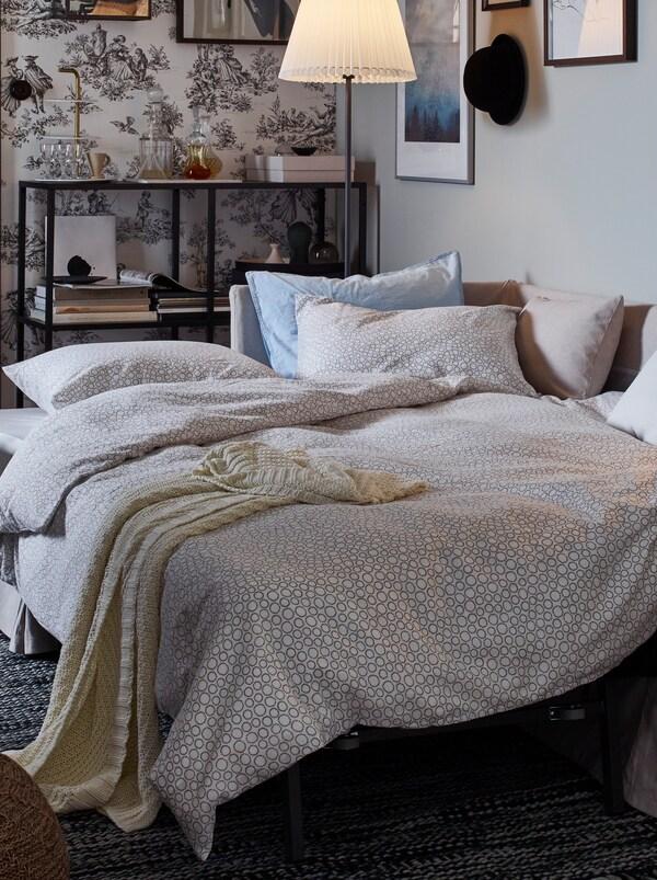Im Hintergrund ist ein Bettsofa zu sehen, das zum Bett umgewandelt ist.