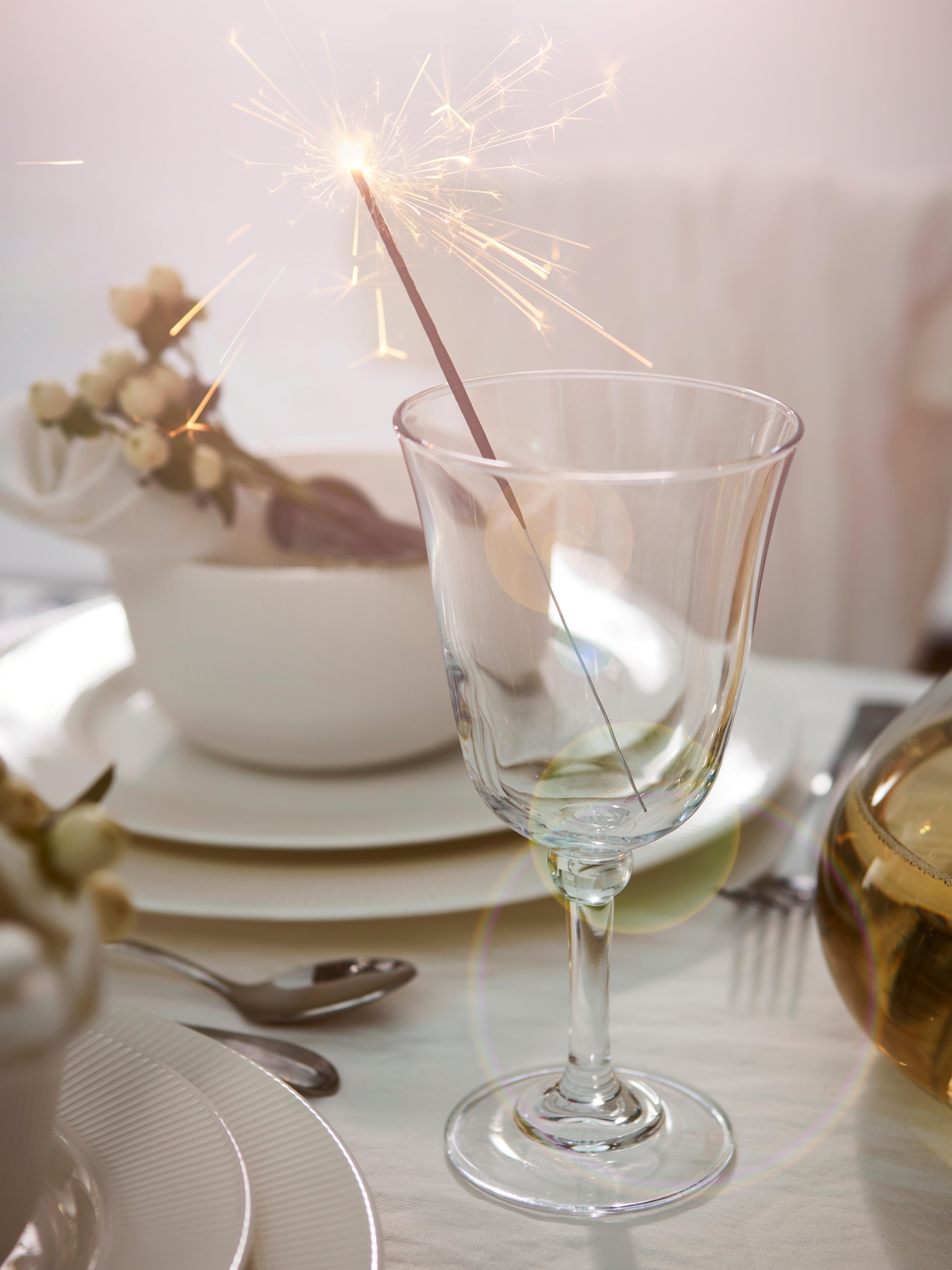 FRAMTRÄDA vinska čaša s penušavcem ispred bele činije na trpezarijskom stolu postavljenom za žurku.