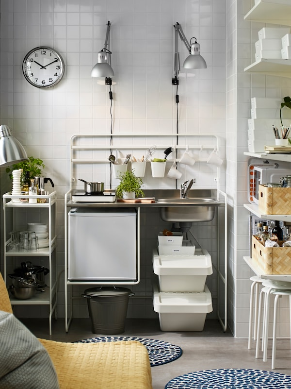 A white SUNNERSTA mini-kitchen against a white tiled wall with two silver wall lamps above it.