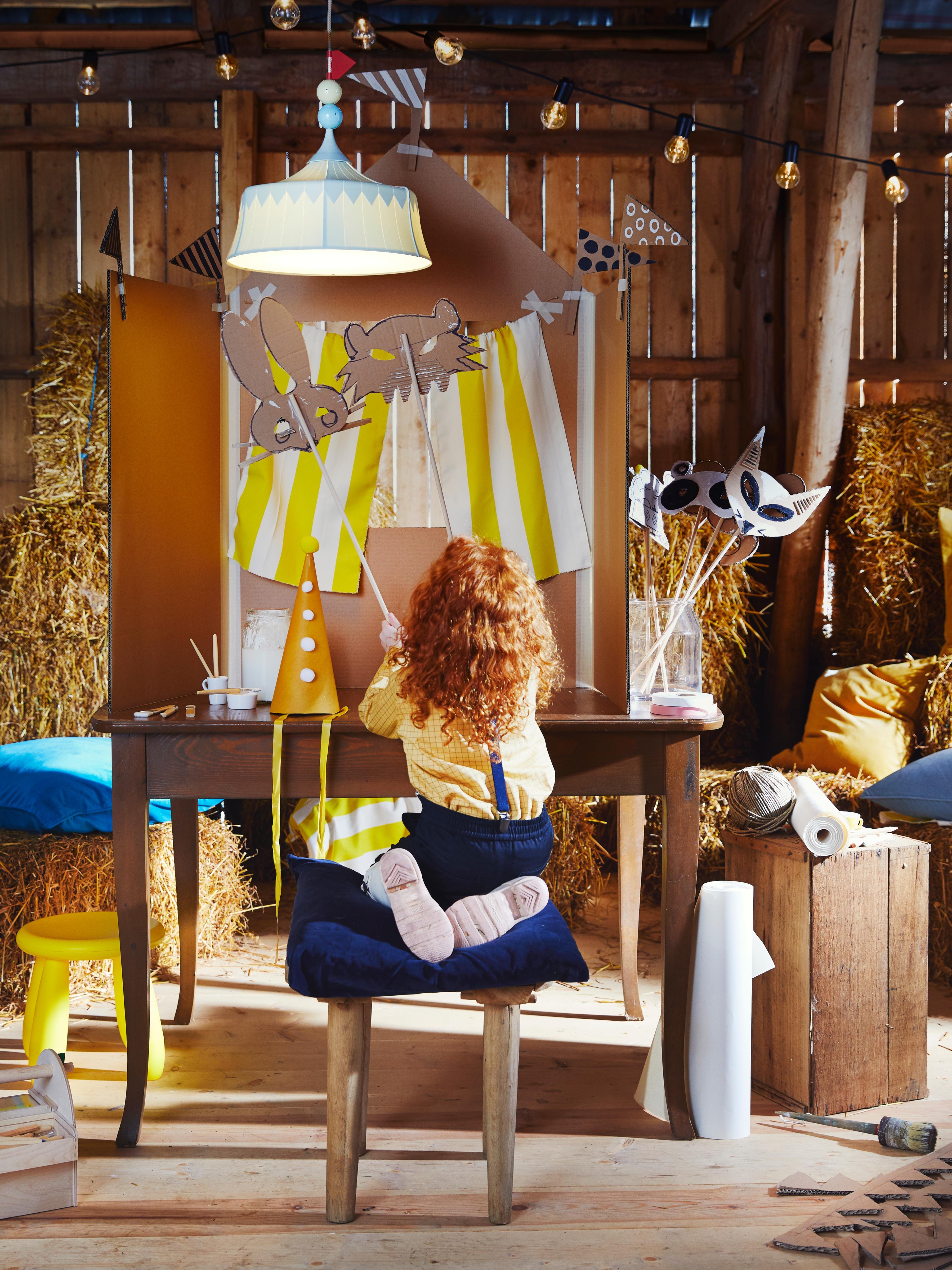 Dans une grange fantaisiste, un enfant présente un spectacle de marionnettes sous une suspension TROLLBO en plastique vert clair en forme de chapiteau.
