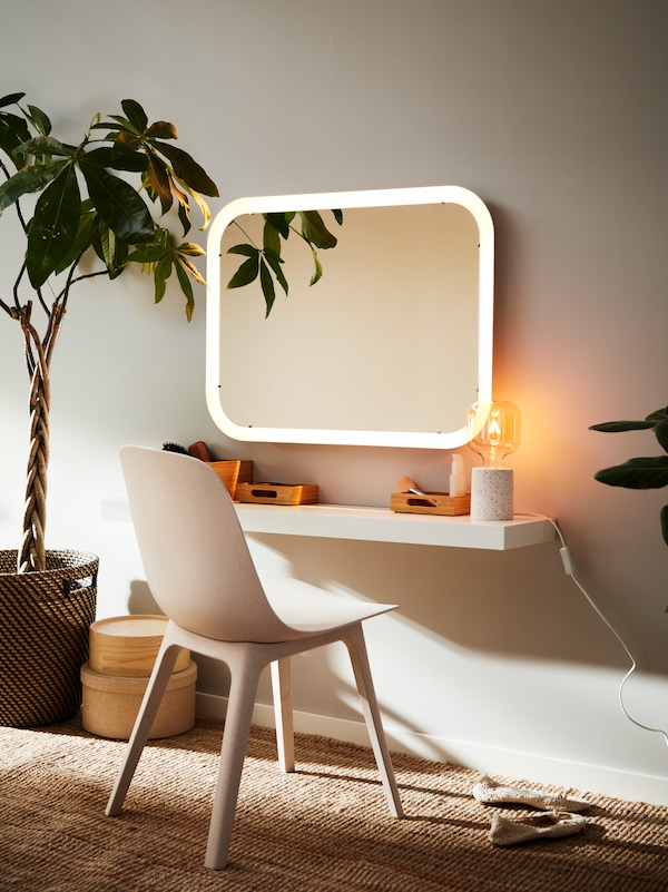 A STORJORM mirror with integrated lighting, a wall shelf with a table lamp and bamboo trays, plus a white/beige ODGER chair.