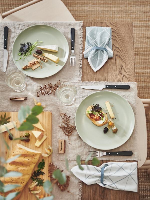 زاوية من طاولة مزينة بمناديل ورقية وأدوات تناول الطعام LIVNÄRA سوداء وطعام احتفالي مقدم على أطباق FÄRGKLAR بلون أخضر غير لامع.
