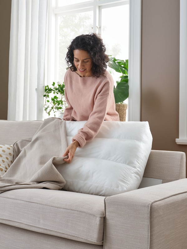 A woman standing huddled over a beige KIVIK sofa, in the middle of changing the cover of one of its back cushions.