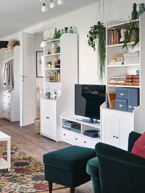 A living room with white HAUGA high cabinets and TV bench along the wall beside a green armchair and footstool.