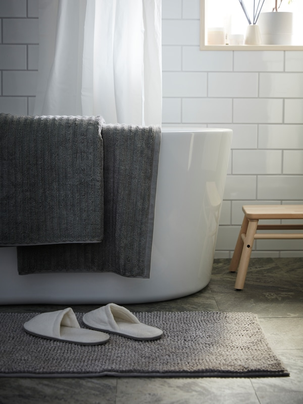 white slippers sat on TOFTBO bathmat, with grey FLODALEN bathsheet draped over the side of a bathtub.