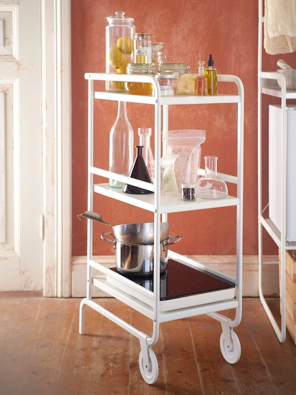 A white SUNNERSTA trolley holding glass jars, bottles, vases and pots standing between a SUNNERSTA mini-kitchen and a door.