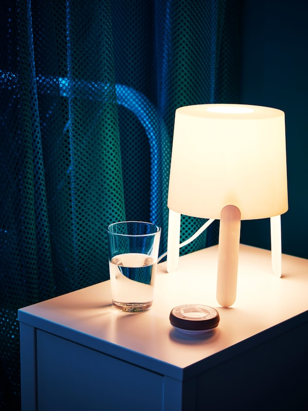 Лампа на ножках стоит на прикроватном столике.