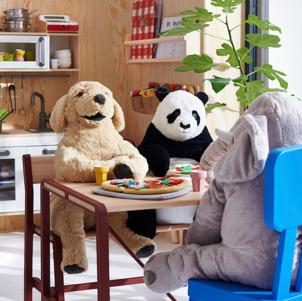 A children's room with animal soft toys sitting on a bench and a MAMMUT chair at an YPPERLIG children's table.
