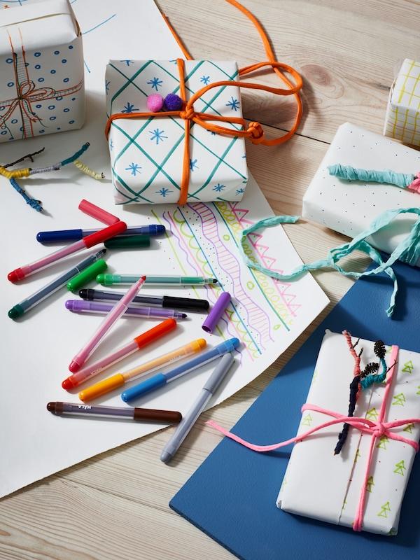 Vegyes színű MÅLA filctollak szétszórva egy papírlapon, körülöttük házilag becsomagolt ajándékok.