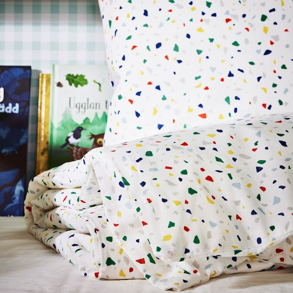A pillow and a duvet inside a white/mosaic patterned MÖJLIGHET quilt cover and pillowcase sit on a child's bed.