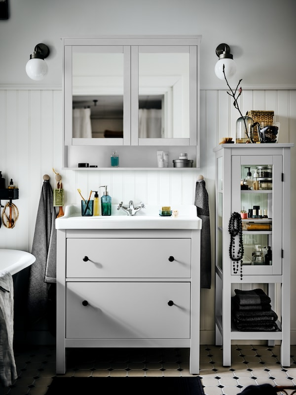 A HEMNES/RÄTTIVIKEN cabinet with sink in a sunny white country-style bathroom with a mirrored door cabinet above.
