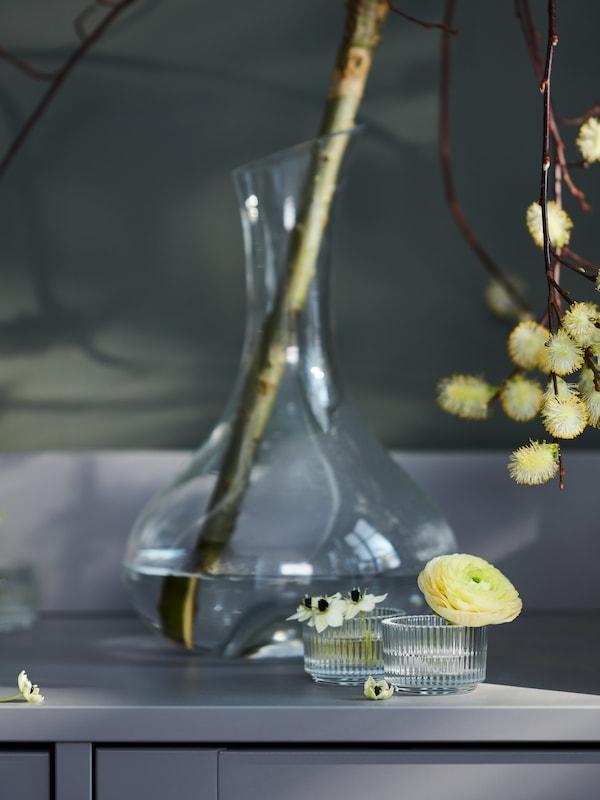 Des photophores FINSMAK en verre clair décorés de fleurs simples devant une carafe STORSINT décorée d'une branche.