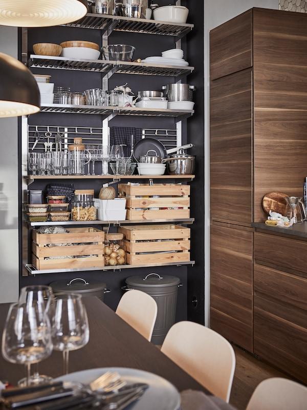 Una cucina con uno scaffale a giorno in acciaio inossidabile con contenitori, articoli per la tavola e tre contenitori in pino.