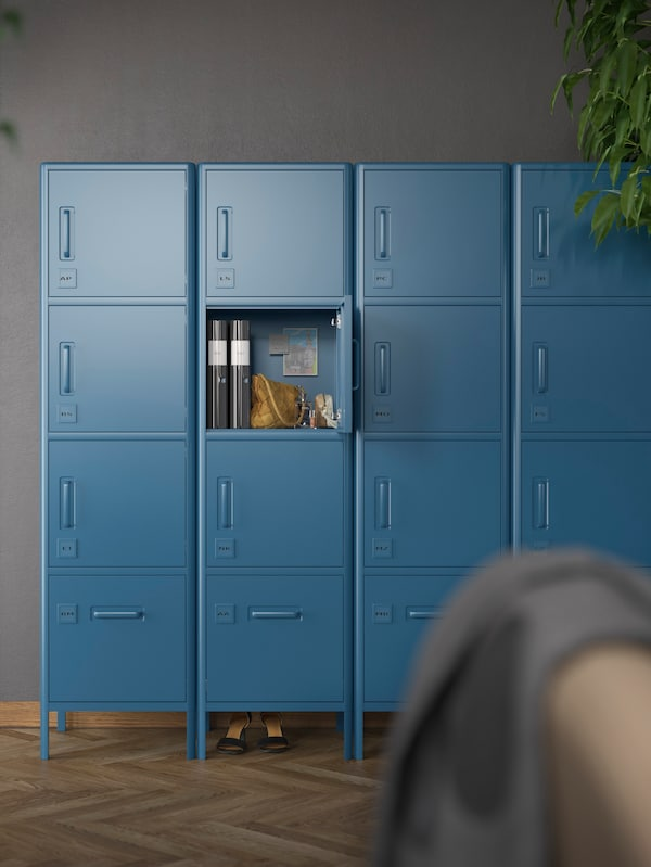 Blue closed storage cabinets against a grayish wall, one of the doors open with files, a bag and various items inside.