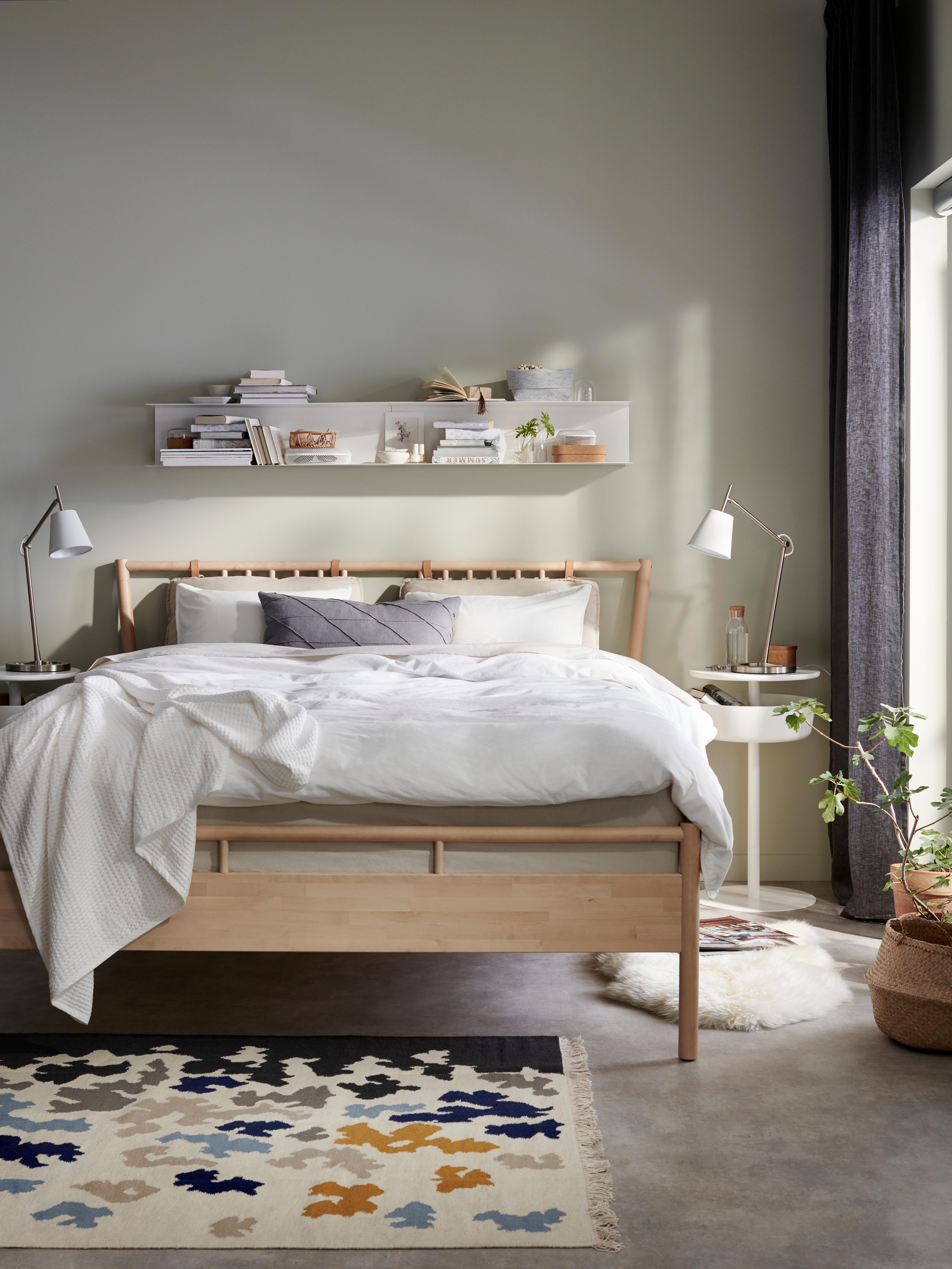 BJÖRKSNÄS okvir kreveta od breze s bijelom navlakom za poplun i prekrivačem uza zid spavaće sobe pored noćnog ormarića.