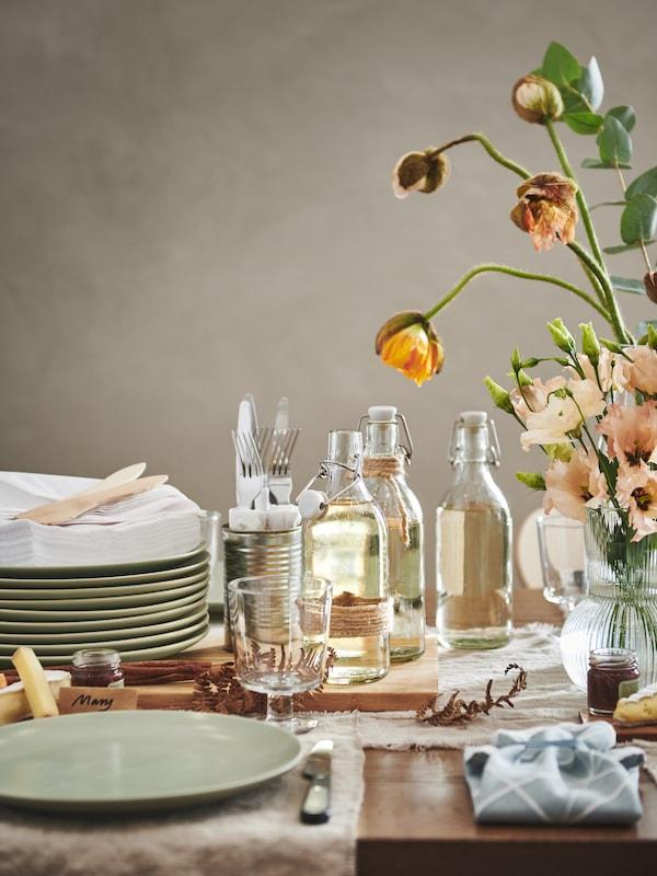 ส่วนของโต๊ะที่จัดไว้สำหรับงานเลี้ยงพร้อมจาน FÄRGKLAR/แฟรีคลาร์ สีเขียวด้าน, ขวด KORKEN/คอร์เก้น, แก้วก้าน IKEA 365+/อิเกีย 365+ และดอกไม้