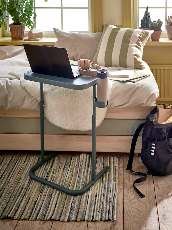 A laptop sits on a turquoise BJÖRKÅSEN laptop stand on a TÅNUM flatwoven rug beside an UTÅKER stackable bed.
