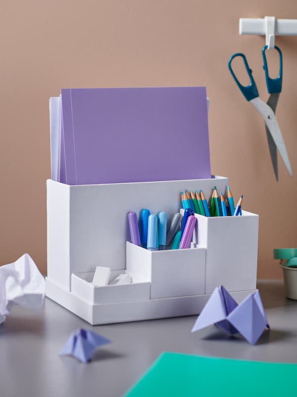 A white desk organizer with colorful markers and pencils inside, also holding violet paper, on a desk surface.