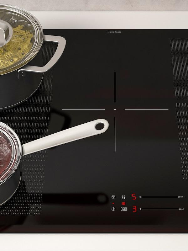 Auf einem BLIXTSNABB Induktionskochfeld werden in einem bedeckten mittelgroßen Topf Nudeln gekocht. Daneben steht eine Pfanne mit Deckel auf einer flexiblen Wärmezone.