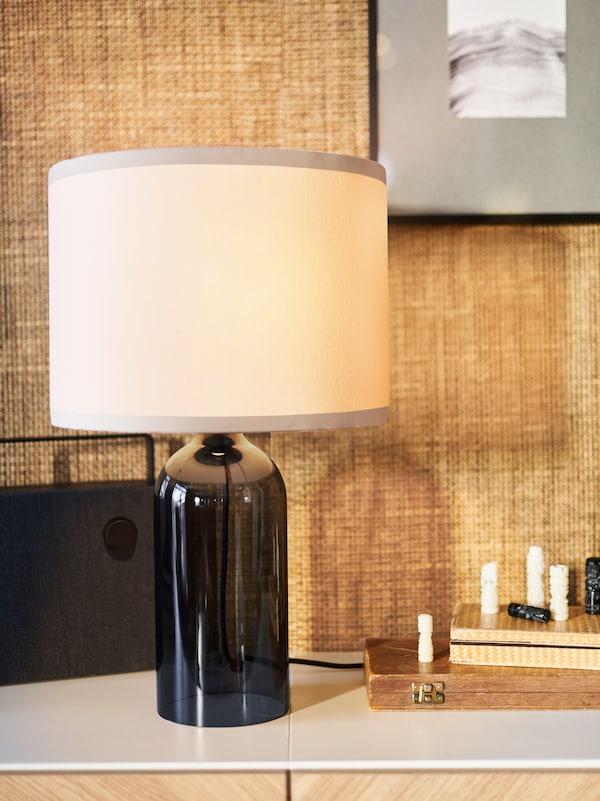 Ei TONVIS bordlampe i røkfarget glass og hvitt står på ei hvit overflate mot en vegg med lysebrun tapet.