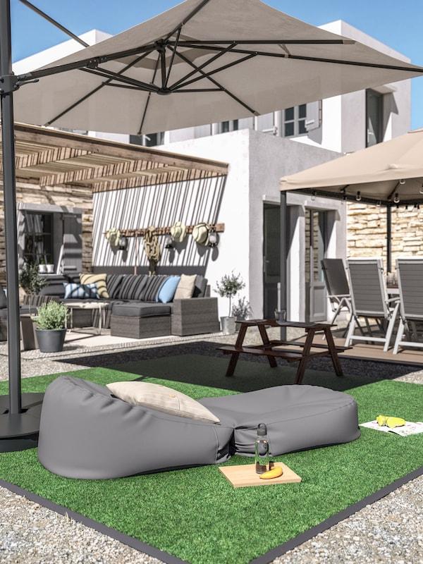 Bodenrost mit Kunstgras, ein grauer Sitzsack mit Kissen, ein Picknicktisch für Kinder und ein grosser, beigefarbener Sonnenschirm.