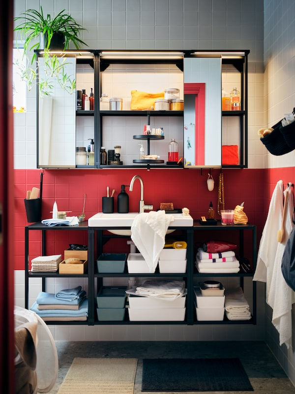 A red-and-white-tiled bathroom with a big ENHET combination with open cabinets, filled with neatly arranged accessories.