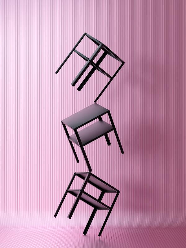 Trois tables de chevet KNARREVIK noires empilées, en équilibre sur un pied, au bout d'un couloir rose aux surfaces ondulées.