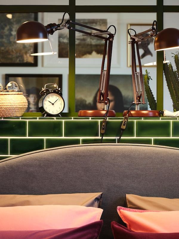Dua lampu kerja berwarna merah gelap terletak di atas dinding separuh berjubin hijau dan menerangi kepala katil berwarna kelabu, bakul yang dibuat daripada rumput laut dan enam bantal.
