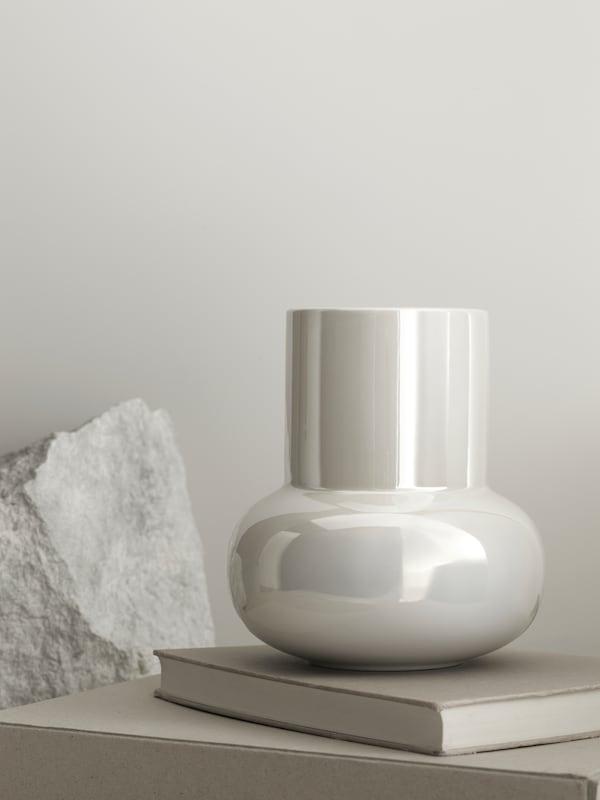 Vaso FNITTRIG bianco iridescente, dalla forma tondeggiante, appoggiato a una superficie con libri e una pietra grezza.