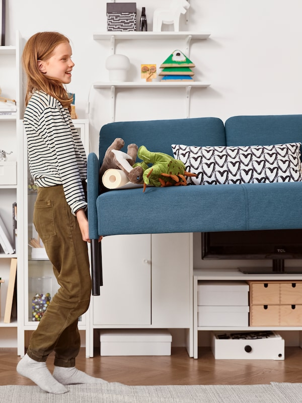 Dinosaurtøjdyr, et hvidt tv-bord, et hvidt vitrineskab og et barn, der løfter den ene ende af en 2-pers. sofa.
