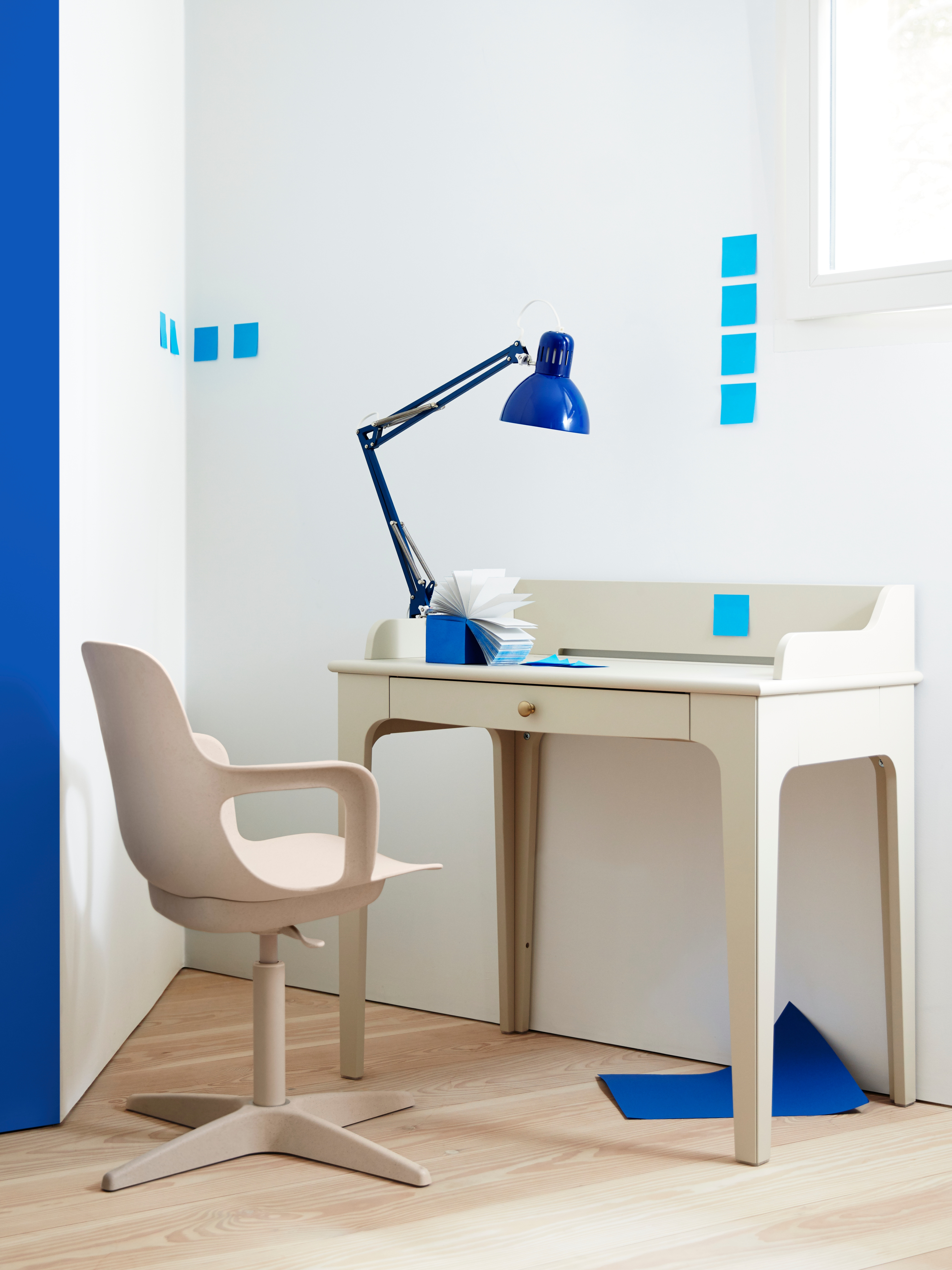 A light beige LOMMARP desk with a drawer and gold knob handle and a blue work lamp on top is in a corner by a swivel chair.