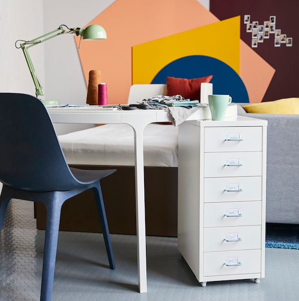 A black desk by a white wall, with decorative objects, a table lamp and other diverse items on the desk.