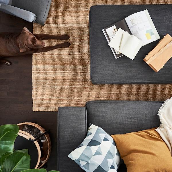 러그와 테이블 소파가 배치된 거실의 모습을 천정에서 바닥쪽으로 바라보는 각도의 이미지입니다.