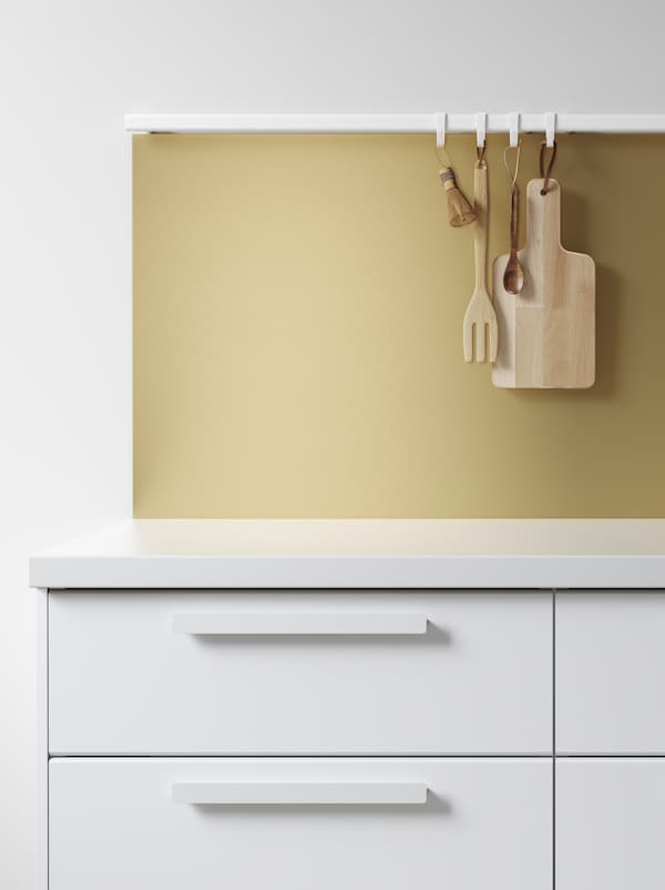 A kitchen with white fronts and worktop and a gold wall panel, with wooden kitchen tools hanging on a rail with hooks.