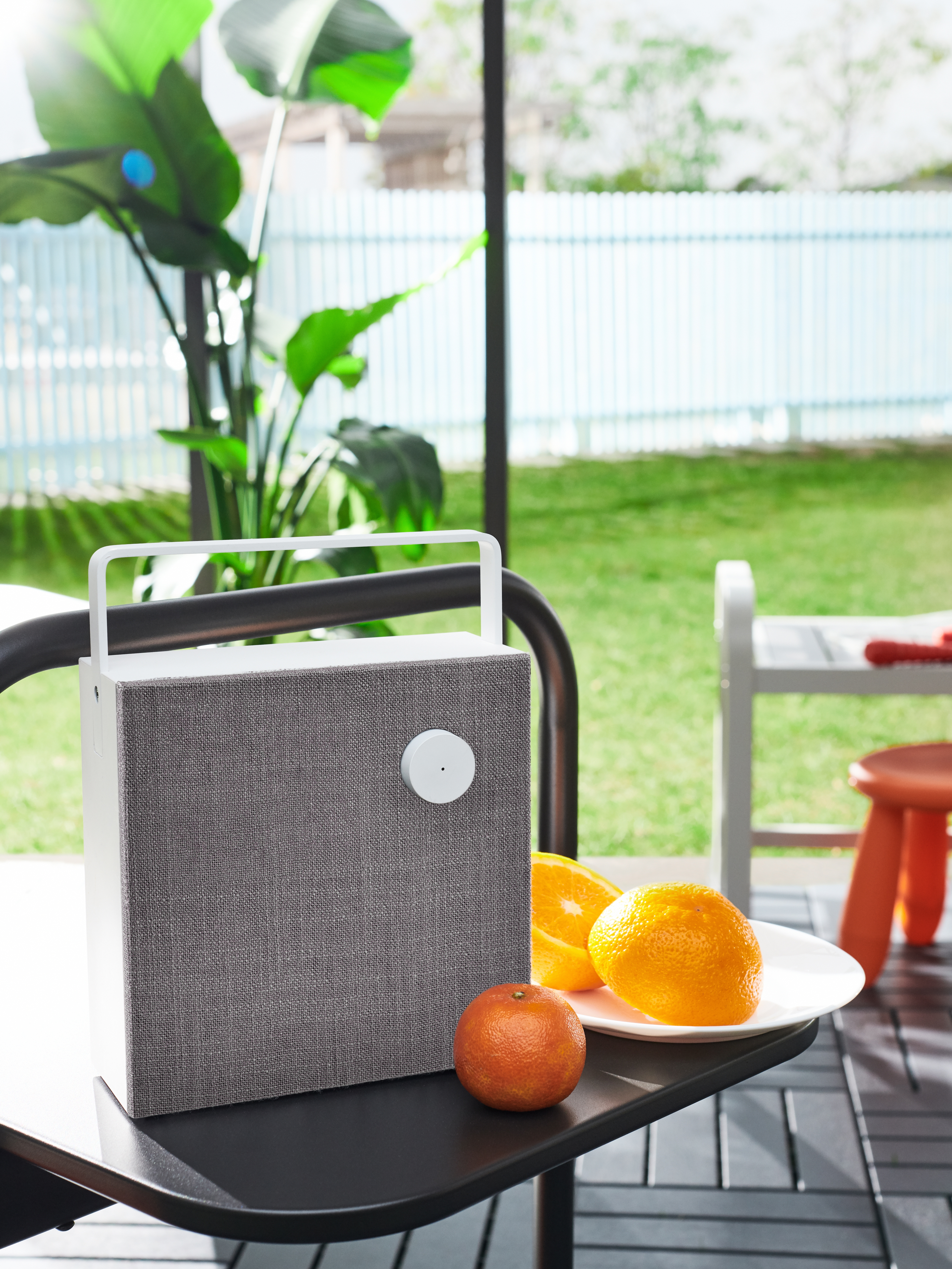 Kanpoko eremua Bluetooth bozgorailuarekin, mahai beltzaren gainean, laranja, landare berdeak eta haurrentzako jostailuak dituen plaka zuriaren ondoan.