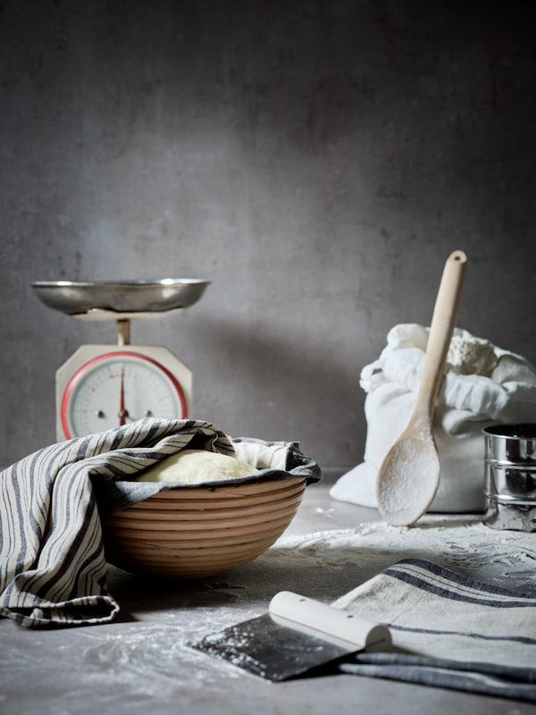 Un coupe-pâte, une cuillère et un bol en bois et une balance de cuisine en métal placés sur un comptoir saupoudré de farine.