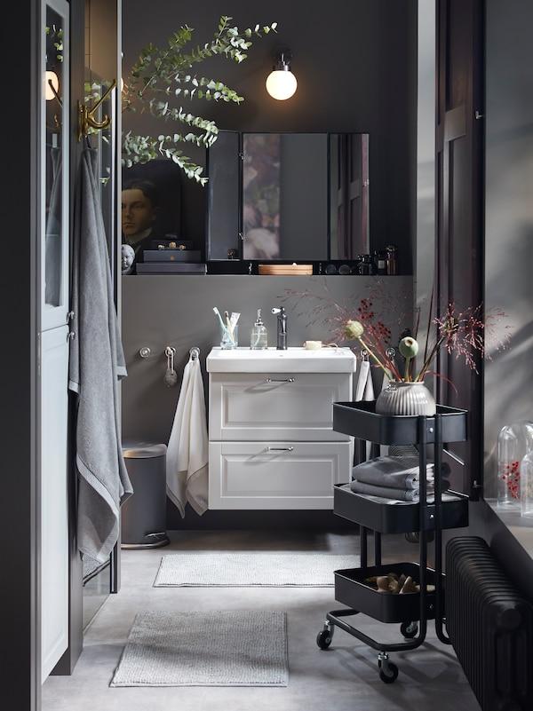 O baie gri închis cu un lavoar gri deschis, un cărucior RÅSKOG negru cu prosoape împăturite și flori decorative.