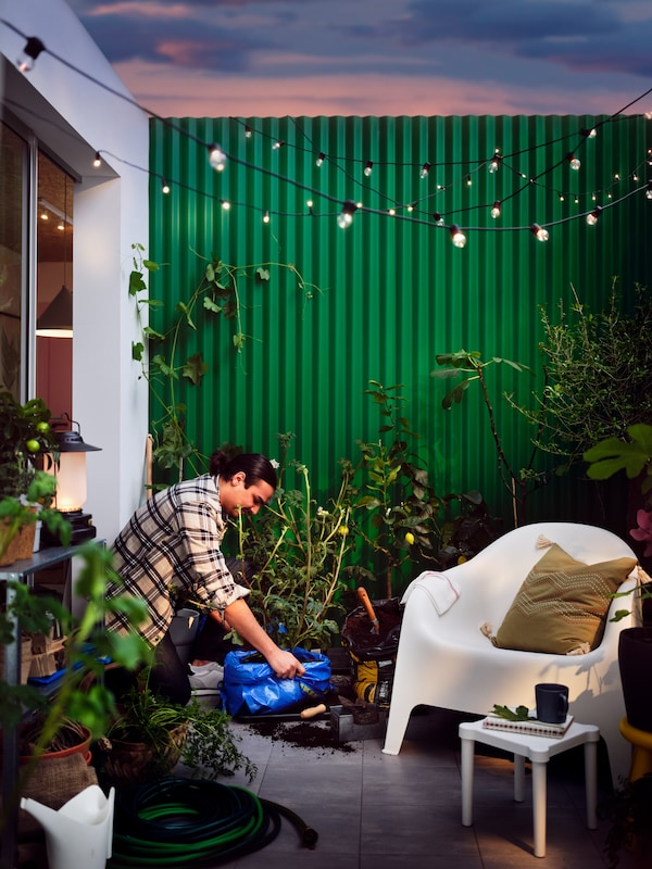 A patio dotted with plants, a white SKARPÖ armchair, an UTTER children's stool, and a black UTSUND LED lighting chain.