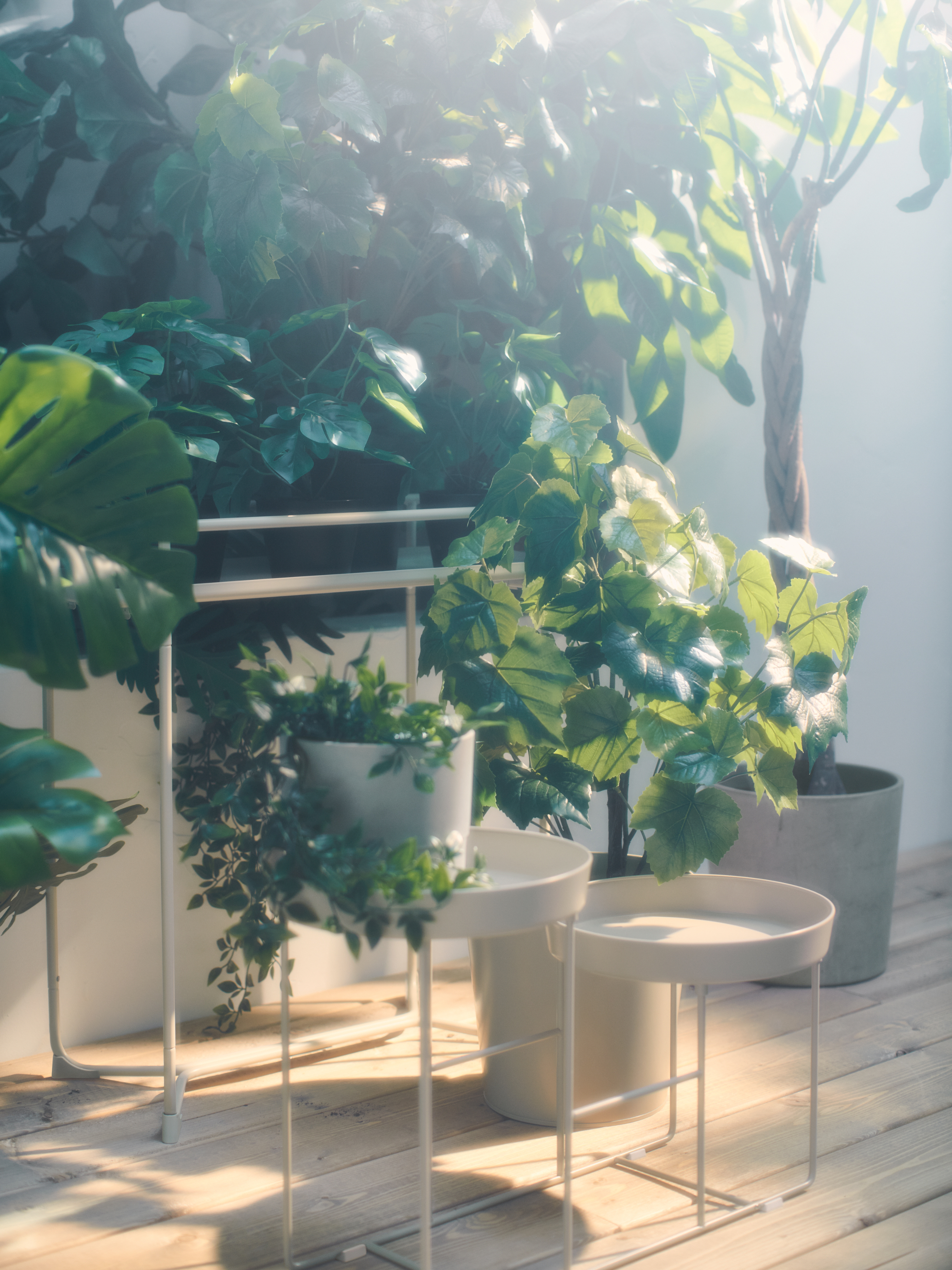 Lots of artificial plants, including a few on a VITLÖK plant stand, create an outdoor garden on a deck.