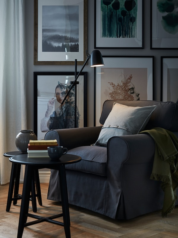 Un fauteuil gris foncé dans un salon au décor foncé. Le fauteuil est éclairé par un lampadaire, près d'une table d'appoint noire.