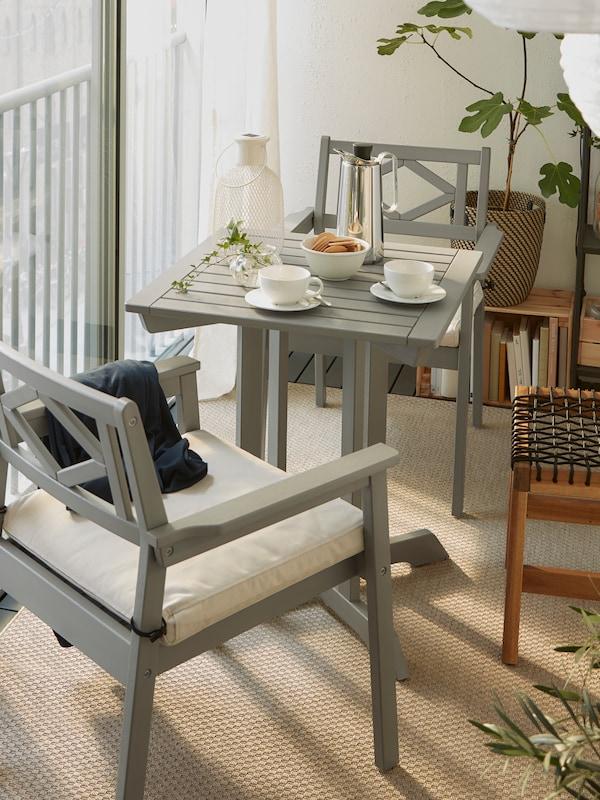 Ein geschlossener Balkon/Wintergarten mit einem Tisch und zwei BONDHOLMEN Armlehnstühlen, einem Hocker und weissen Hängeleuchten