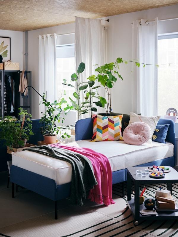 A BLÅKULLEN upholstered bed frame with headboard and bedding including white/dark blue KVASTFIBBLA bed linen.