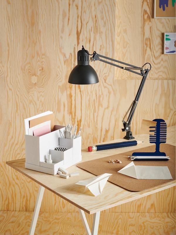 Schwarze TERTIAL Arbeitsleuchte an einem holzfarbenen Schreibtisch montiert.