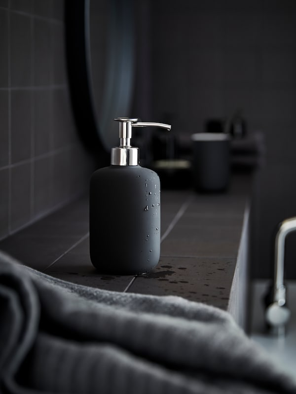A close-up of a dark grey EKOLN soap dispenser on a dark-tiled shelf in a dark bathroom.
