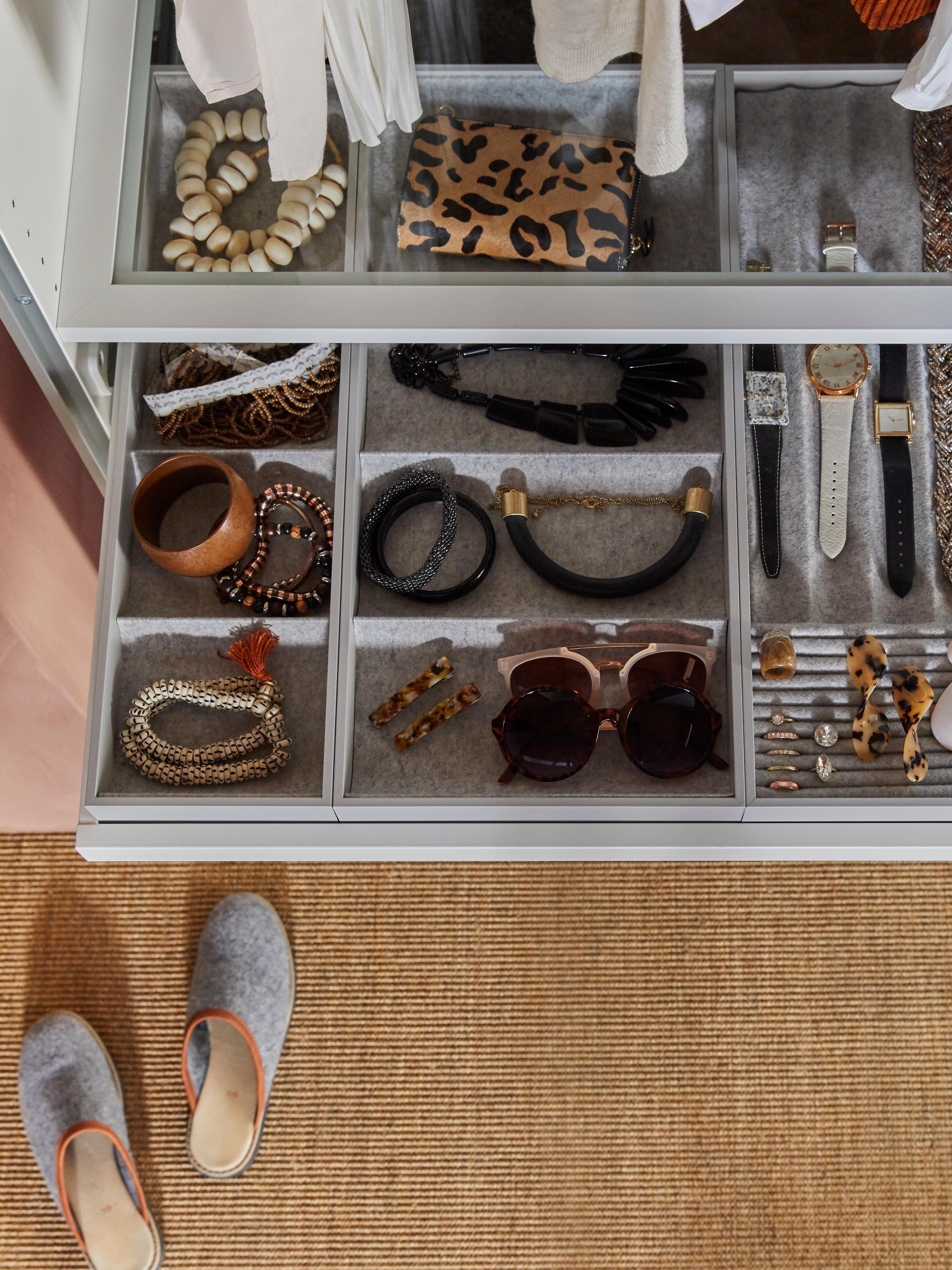 Graue KOMPLEMENT Boxen, gefüllt mit unterschiedlichen Accessoires wie Handtaschen, Ketten, Armreifen und Uhren.
