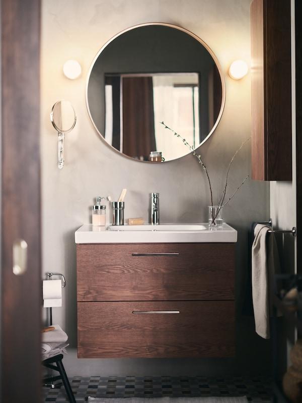 Casa de banho com paredes verdes, com um móvel de lavatório GODMORGON castanho. Na parede um espelho redondo ladeado por dois candeeiros de parede.
