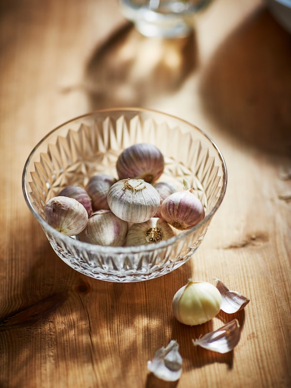 Wooden surface with a clear-glass SÄLLSKAPLIG bowl filled with single-clove garlic, one half-peeled lying beside.