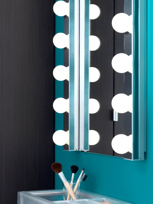 Two wall lamps with a row of LED-bulbs, illuminating a bathroom mirror on a green wall, plus a storage unit below.
